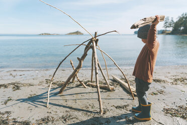 Boy playing on a the beach, building a drift wood fort - CMSF00020