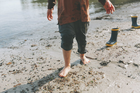 Boy playing on a the beach, walking barefoot in the mud - CMSF00023