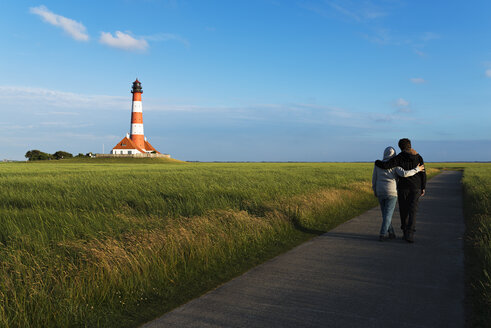 Germany, Westerhever, couple strolling along lighthouse - MKFF00483