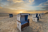 Germany, Sylt, North Sea, sandy beach with hooded beach chairs in sunset - MKFF00486