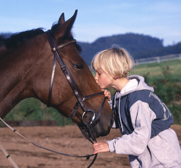 Girl kissing a horse affectionately - WWF04914