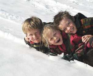 Group picture of three happy children in snow - WWF04917