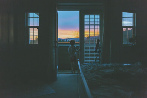 Little boy standing in bedroom door, watching sunset - CMSF00043