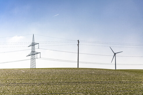 Germany, Baden-Wuerttemberg, Taubertal, power pylons in field - EGBF00293