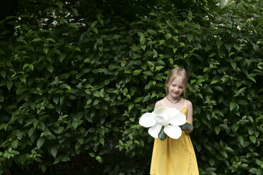 Smiling little girl with oversized white magnolia blossom - EYAF00085