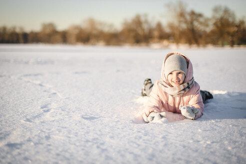 Portrait of little girl lying in snow field - EYAF00097