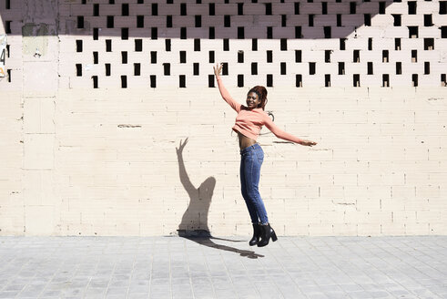 Happy young woman jumping in the air - IGGF00958