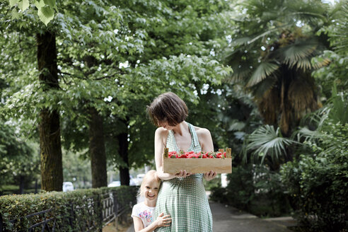 Woman with her daughter holding crate with strawberries - EYAF00111