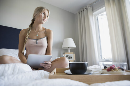 Pensive woman with digital tablet and breakfast bed - HEROF34380