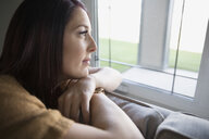 Pensive woman on sofa looking out window - HEROF34395