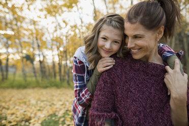 Portrait mother and daughter hugging in autumn park - HEROF34476