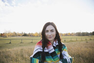 Portrait brunette young woman wrapped in a blanket in field - HEROF34479