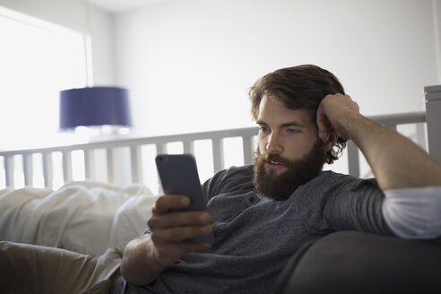 Man texting with cell phone on sofa - HEROF34488