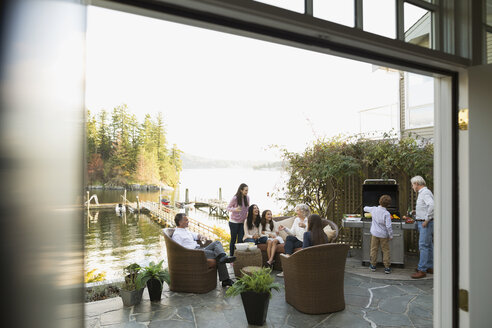 Multi-generation family barbecuing and relaxing lakeside patio - HEROF34509