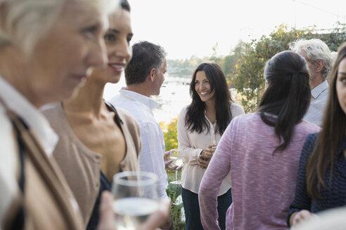 Multi-generation family talking on patio - HEROF34512