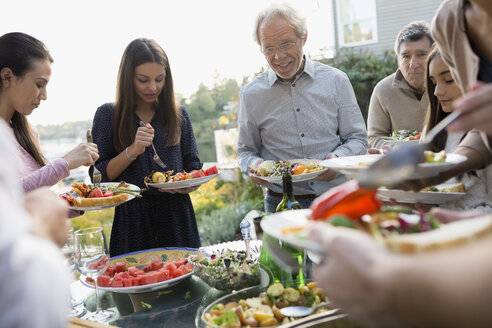 Multi-generation family serving food at buffet patio - HEROF34518