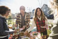 Neighbors enjoying potluck in sunny front yard - HEROF34539