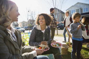 Neighbors enjoying potluck in sunny front yard - HEROF34545