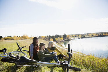 Multi-generation family resting bicycles in sunny field - HEROF34563