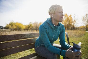 Jogger with headphones water bottle resting park bench - HEROF34569