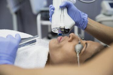 Woman receiving laser facial treatment - HEROF34611