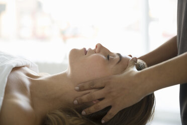 Serene woman with eyes closed receiving head massage - HEROF34671