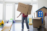 Playful boy dancing with cardboard box on head - HEROF34695