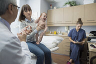 Pediatrician preparing injection for baby in examination room - HEROF34704