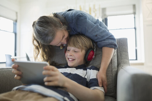 Mother kissing son with headphones using digital tablet - HEROF34713