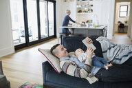 Father and son using digital tablet on sofa - HEROF34773