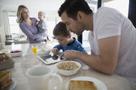 Father and son using digital tablet at breakfast - HEROF34782