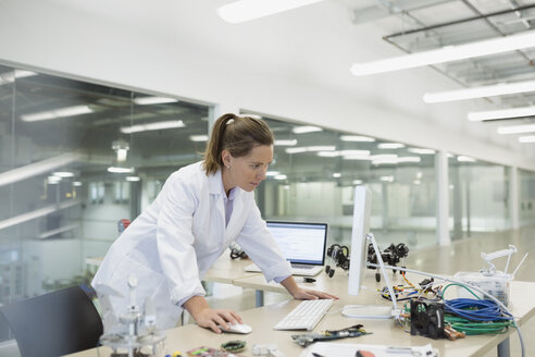 Engineer working at computer with robotics in factory - HEROF34821