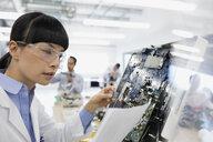 Engineer with paperwork examining circuit board - HEROF34830