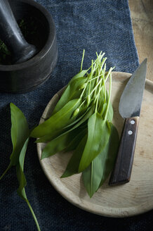 Ramson and knife on wooden board, mortar and bowl of pine nuts - ASF06364