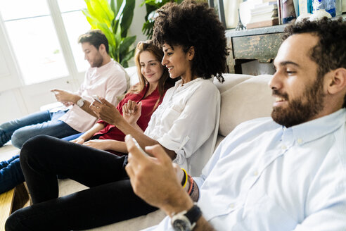Friends sitting on couch, working casually together, using smartphones - GIOF06110