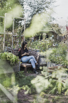 Woman using smartphone in urban garden - VGPF00006