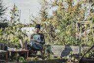 Smiling man reading book in urban garden - VGPF00009