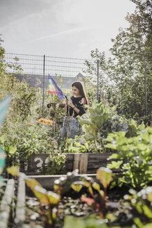 Woman using smartphone in urban garden - VGPF00015