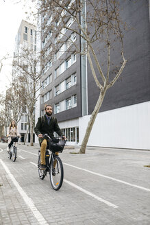 Couple riding e-bikes in the city - JRFF02888