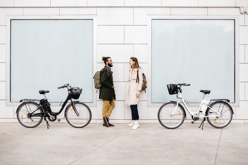 Man and woman with e-bikes standing at a building talking - JRFF02894