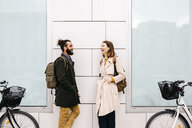 Man and woman with e-bikes standing at a building talking - JRFF02897