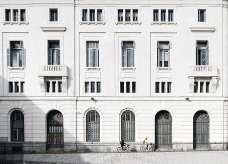 Couple riding e-bkes in the city passing a building - JRFF02900