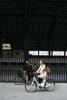 Couple riding e-bikes in the city - JRFF02906