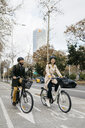 Couple riding e-bikes in the city on bicycle lane - JRFF02909