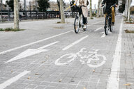 Couple riding e-bikes in the city on bicycle lane - JRFF02912