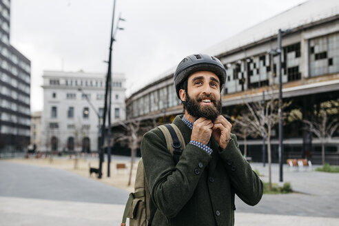 Portrait of smiling man putting on bicycle helmet in the city - JRFF02915