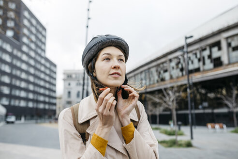 Portrait of woman putting on bicycle helmet in the city - JRFF02918