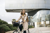 Portrait of woman riding e-bike in the city - JRFF02921