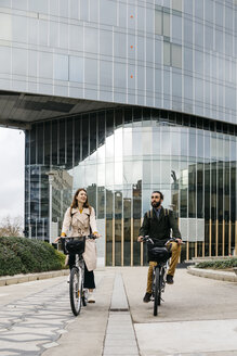 Couple riding e-bikes in the city - JRFF02924