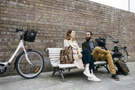 Couple sitting on a bench next to e-bikes talking - JRFF02930